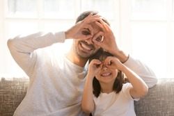 Pretty family father adorable daughter sitting on sofa do funny faces making with fingers eyewear shape like glasses looking through binoculars, have fun with child free time play tricks fool concept