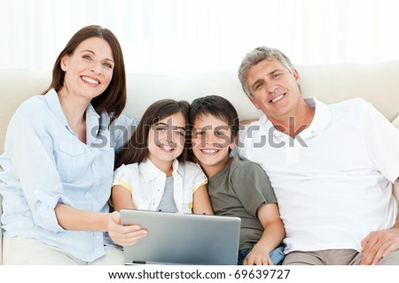 Pretty family looking at the camera at home - stock photo