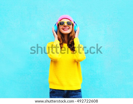 Pretty fashion cool smiling girl listening to music in headphones wearing a colorful pink hat, yellow sunglasses and sweater over blue background