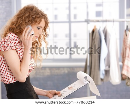 Pretty fashion designer working in office using mobile phone.?
