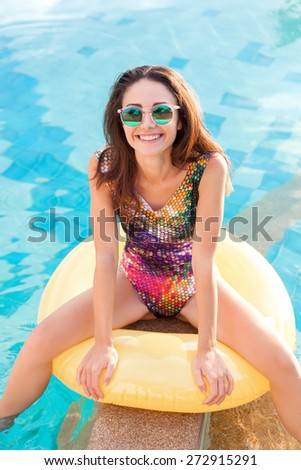 Pretty fashion sport style woman smiling and relaxing in the pool in summer. Outdoor portrait of cute girl in sunglasses in tropic resort