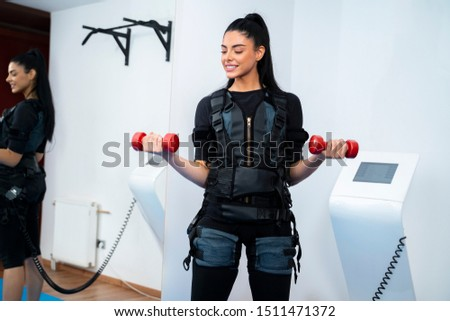 Pretty female athlete exercising with small dumb bells on ems machine
