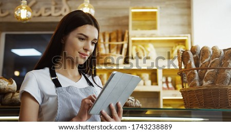 Pretty female baker working in bakery shop using digital tablet computer while standing at counter.