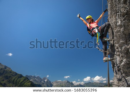 Pretty, female climber on a via ferrata - climbing on a rock in Swiss Alps Foto d'archivio ©