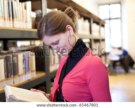 pretty female college student in a college library (shallow DOF; color tuned image)