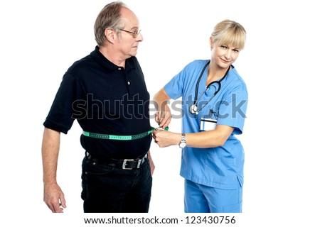 Pretty female doctor measuring waist of senior surprised man.