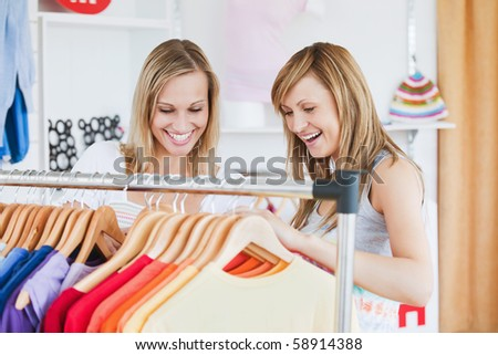 Pretty female friends doing shopping choosing shirts in a clothes store