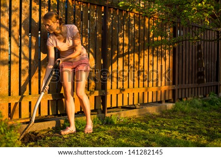 Pretty female gardener taking care of her lovely garden on a lovely spring day - cutting branches, double digging/loosening the soil with a spade