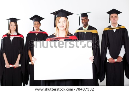 pretty female graduate holding white board with classmates in background