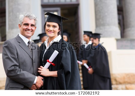 pretty female graduate with her father at university graduation