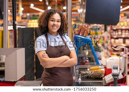 Pretty female in apron standing by cashbox in supermarket and crossing arms by chest on background of shelves with food products