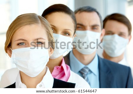 Pretty female in protective mask looking at camera with row of partners behind