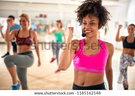 Pretty female instructor with headset in fitness class exercise with group