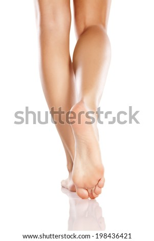 pretty female legs and bare feet on white background