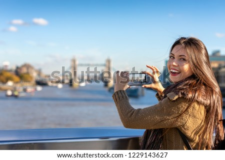 Pretty female London tourist is taking pictures of the Tower Bridge during her sightseeing trip through the city