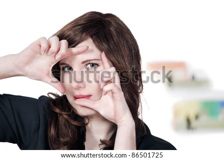 Pretty female looking through hand frame - stock photo
