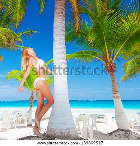 Pretty female next to palm tree, sexy girl wearing bikini, luxury tropical resort, enjoying warm sunny day, woman on paradise beach, summer vacation concept