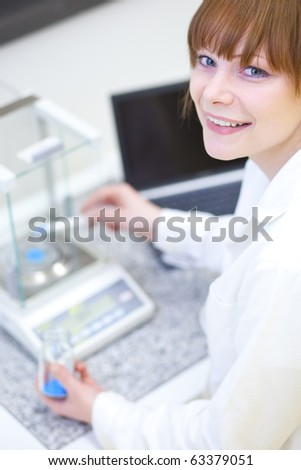pretty female researcher working in a lab - stock photo