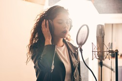 Pretty female singer recording in music studio
