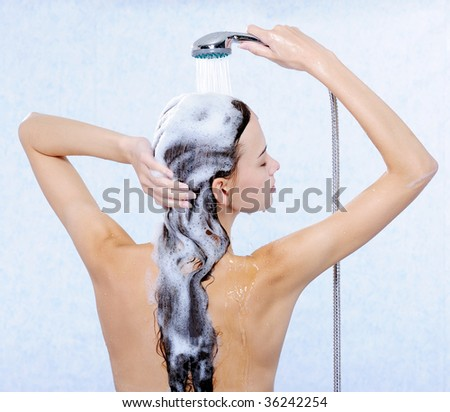 Pretty female standing back and washing her long hair