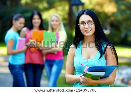 pretty female student outdoors with a group of people on the background