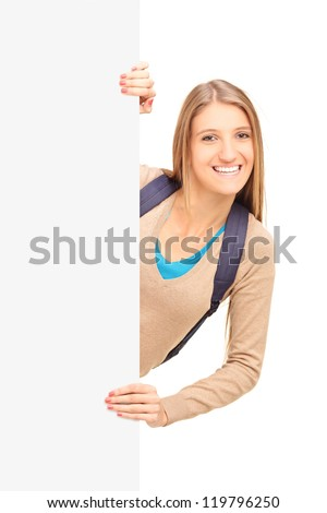 Pretty female student posing behind a white panel isolated on white background