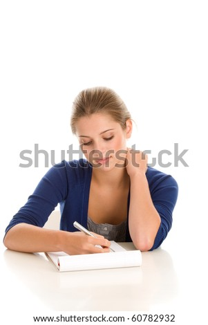 Pretty female student sitting behind desk with notepad and pen isolated on white background