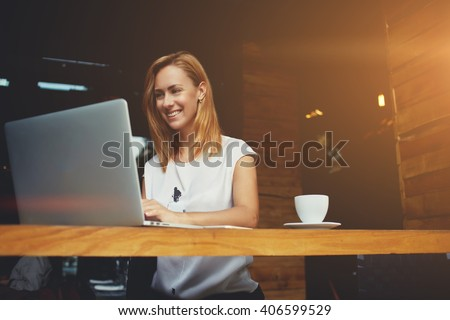 Pretty female student with cute smile keyboarding something on net-book while relaxing after lectures in University, beautiful happy woman working on laptop computer during coffee break in cafe bar stock photo