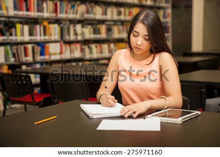 Pretty female university student doing some work at the school library