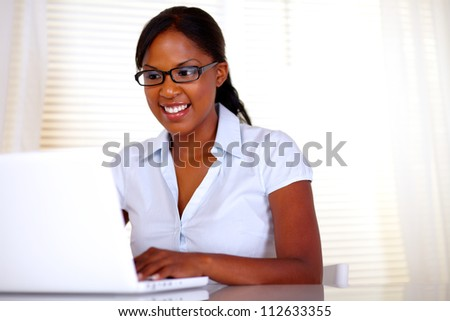 Pretty female with black glasses working on laptop at office - copyspace