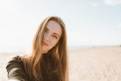 Pretty female with long hair, blonde takes selfie photo on mobile phone. Beautiful woman looking at camera and tilting head. Sandy beach in unny day in ocean or sea coastline