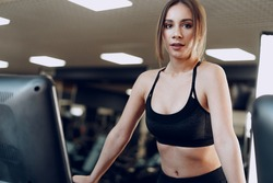 Pretty fit woman in black sportrswear training on a treadmill