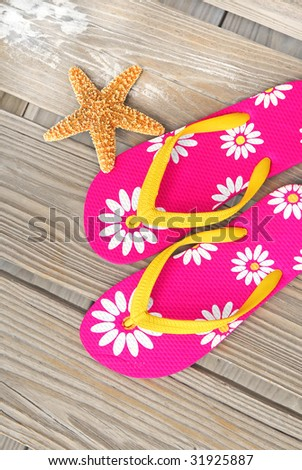 Pretty flip flop sandals on beach dock by starfish - stock photo