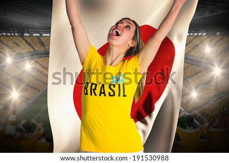 Pretty football fan in brasil t-shirt holding japan flag against vast football stadium with fans in yellow