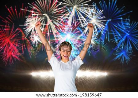 Pretty football fan in white cheering against fireworks exploding over football stadium