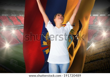 Pretty football fan in white cheering holding ecuador flag against vast football stadium with fans in yellow and red