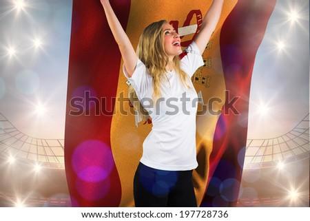 Pretty football fan in white cheering holding spain flag against large football stadium under blue sky