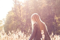 Pretty fresh blonde young woman walking outdoors in the sun and high grass and wearing a coat