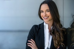 Pretty, friendly, charming, likable brunette businesswoman head shot portrait at the office workplace, happy and smiling