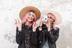 Pretty funny girl with pink hair with smile in straw hat in fashion jacket stands next to sister with modern camera in jacket and shows sign of peace. Lovely happy girls takes positive snapshots.