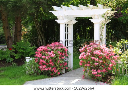 Pretty garden arbor with pink flowers. Also available in vertical. - stock photo