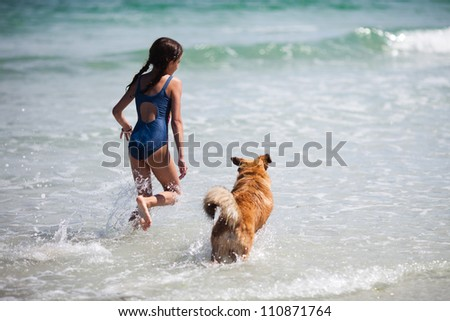 pretty girl and her dog running on the water at the beach