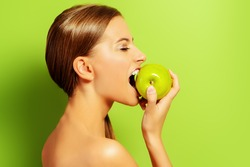 Pretty girl biting fresh apple over green background. Healthy lifestyle. Healthy eating. Fruits and vegetables.