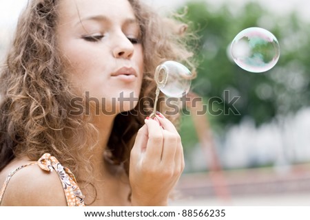 Pretty  girl blowing bubbles soap in nature.