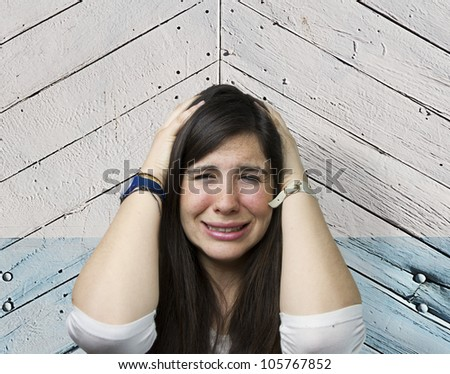 pretty girl crying over wooden background