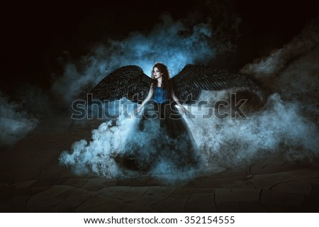 Stock Photo Pretty girl-demon with black wings behind her back