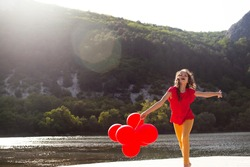 Pretty girl dressed red  t-shirt and yellow jeans, jumping in the nature with fun against the beautiful view of mountain, forest and lake, Preteen kid holding balloons