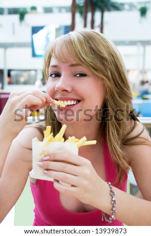 Pretty girl eating french-fries