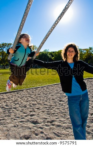 pretty girl enjoys swinging while her mother pushes her during a clear sunny day