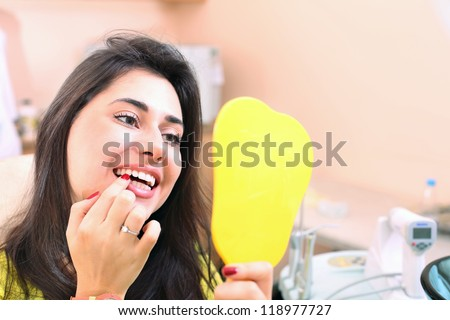 Pretty girl examines her teeth in the mirror